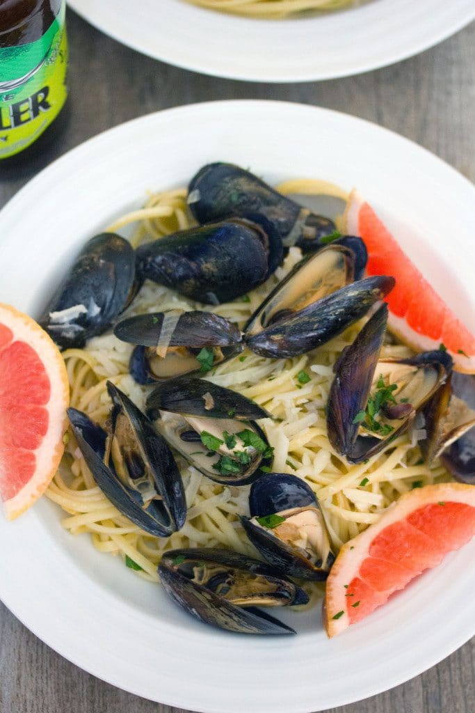 Overhead view of white bowl of grapefruit shandy mussels over linguine with grapefruit wedge garnish and bottle of beer in the background