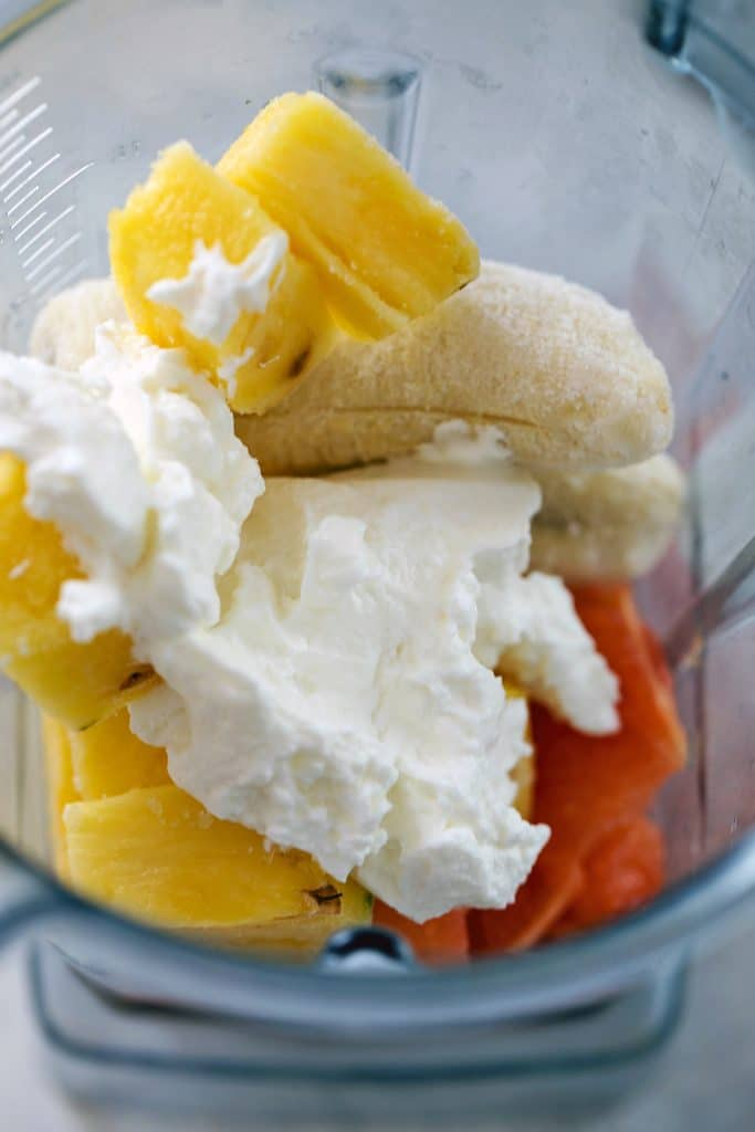 Blender with grapefruit sections, pineapple cubes, frozen banana, and Greek yogurt in it