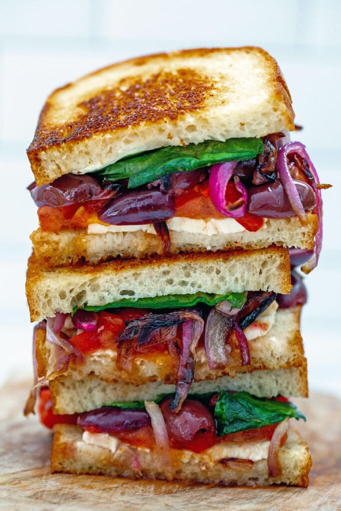 Three halves of greek grilled cheese sandwich stacked on each other with feta, olives, tomato, red pepper, red onion, and spinach