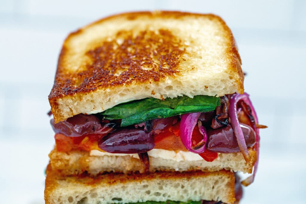 Landscape closeup of a half of a Greek grilled cheese sandwich with feta, red peppers, red onion, kalamata olives, tomato, and spinach peeking out