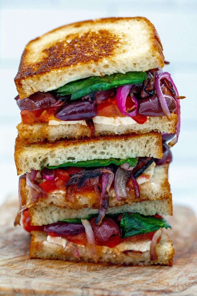 Greek grilled cheese sandwich halves stacked on each other with feta, red onion, kalamata olives, tomatoes, spinach, and red peppers peeking out