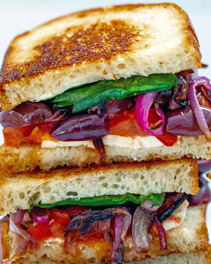 Closeup of two halves of a Greek grilled cheese sandwich stacked on each other with feta, red peppers, red onion, kalamata olives, tomato, and spinach peeking out