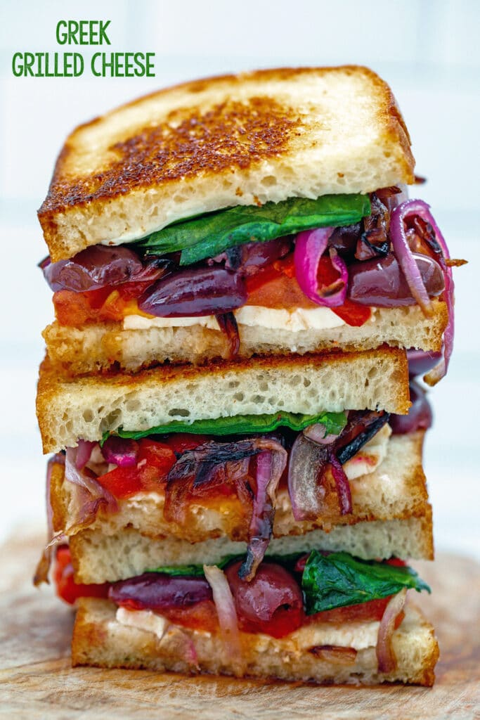 Three halves of greek grilled cheese sandwich stacked on each other with feta, olives, tomato, red pepper, red onion, and spinach, with recipe title at top