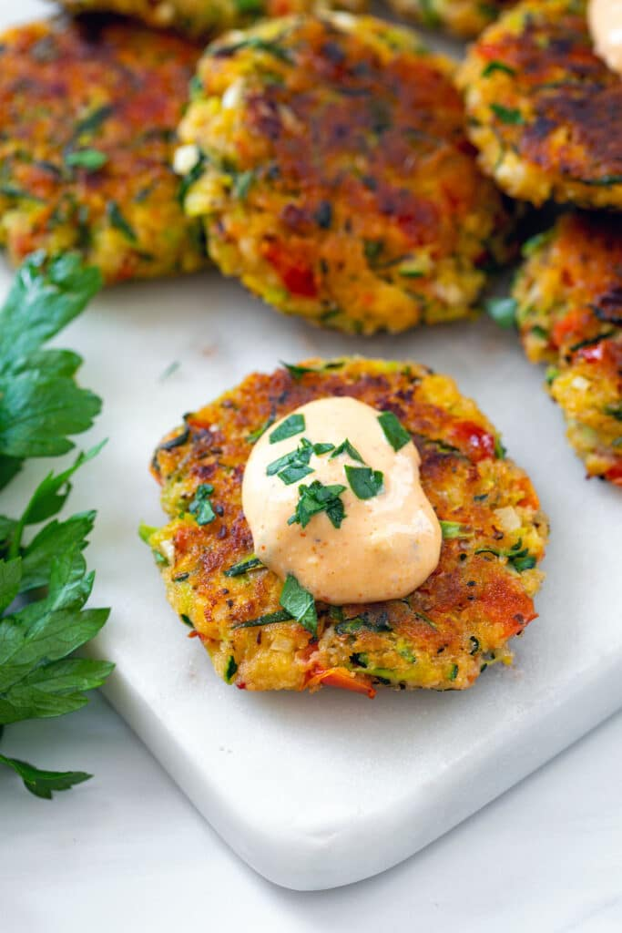 Closeup overhead view of a Greek zucchini cake topped with spicy tomato feta dip and parsley