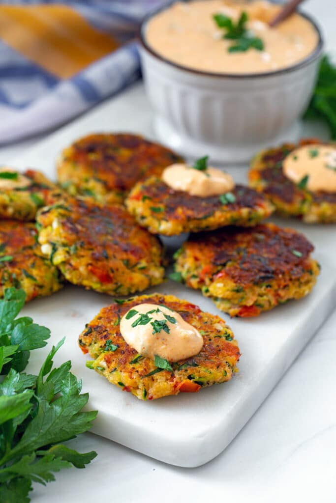 View of Greek zucchini cakes topped with tomato feta dip on a marble platter with parsley all around