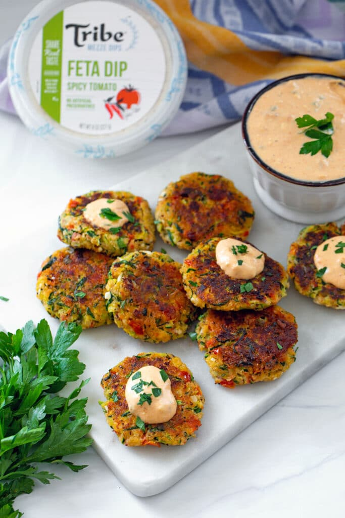 Greek zucchini cakes on a marble platter with package of Tribe Mezze dip and bowl of spicy tomato feta dip in background with parsley all around