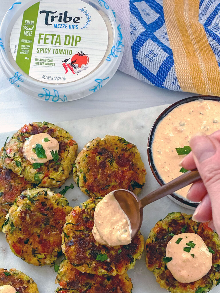 Overhead view of Greek zucchini cakes with a spoonful of spicy tomato feta dip being put on top with Tribe Mezze dip package in background