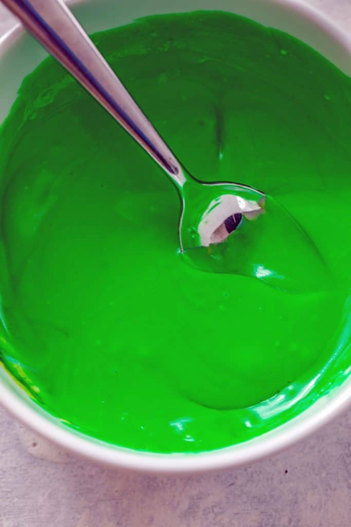 Overhead view of bright green Irish whiskey frosting in a bowl