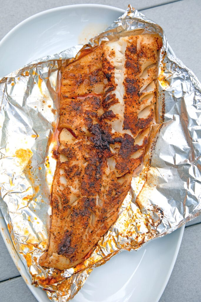 Overhead view of cod just off the grill on foil