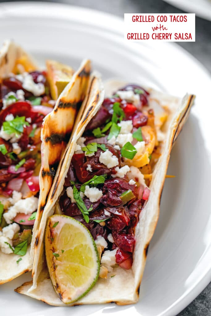 Overhead closeup view of grilled cod tacos with cherry salsa, cheese, scallions, onions, and lime with recipe title at top