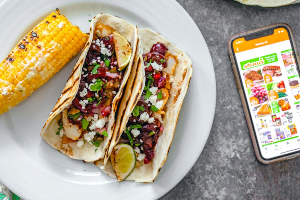 Bird's eye view of two grilled cod tacos with grilled cherry salsa with side of corn on the cob with iPhone open to Shaw's Supermarket app on the side