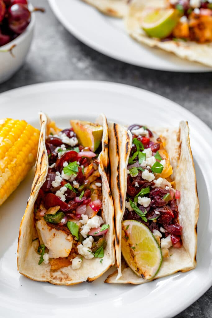 Head-on view of two grilled cod tacos with grilled cherry salsa