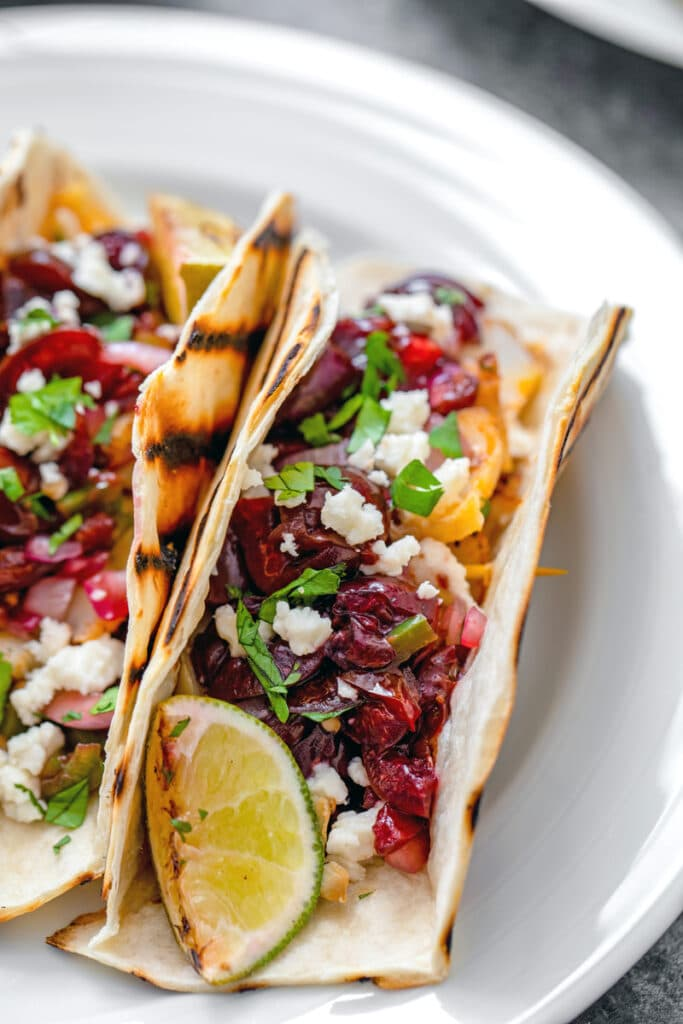 Overhead closeup view of grilled cod tacos with cherry salsa, cheese, scallions, onions, and lime