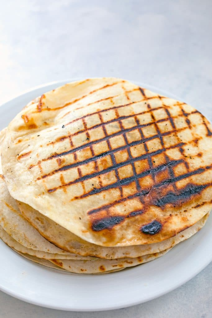 Flank steak quesadillas with criss-cross grilled marks stacked on a white plate before being sliced