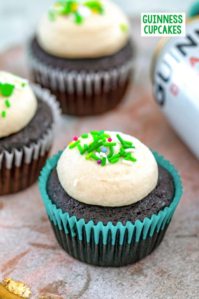 Head-on view of a Guinness cupcake with Guinness frosting and green sprinkles with more cupcakes and can of Guinness in the background with recipe title at top