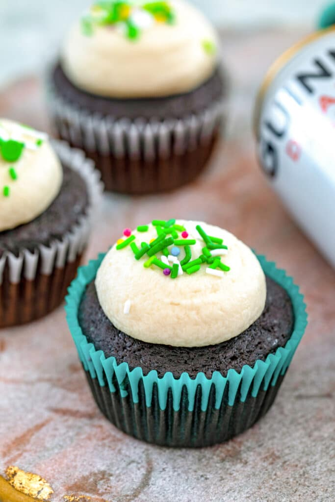 Head-on view of a Guinness cupcake with Guinness frosting and green sprinkles with more cupcakes and can of Guinness in the background