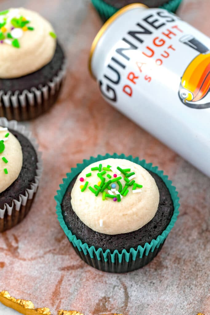 Overhead view of a Guinness cupcake with buttercream and green sprinkles with more cupcakes and can of Guinness in background