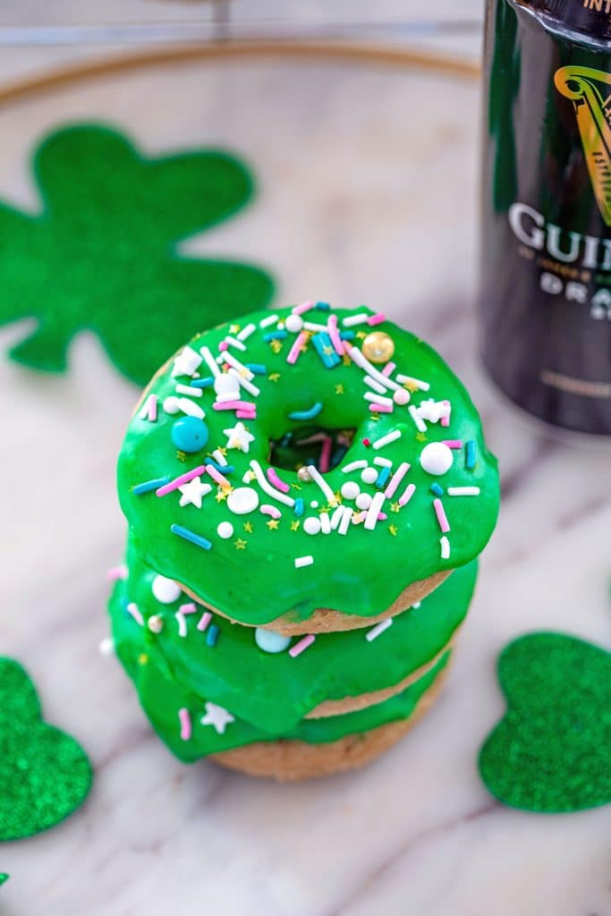 Overhead view of a stack of Guinness doughnuts with bright green Irish whiskey frosting and sprinkles on a marble surface with glitter shamrocks and can of Guinness beer in the background