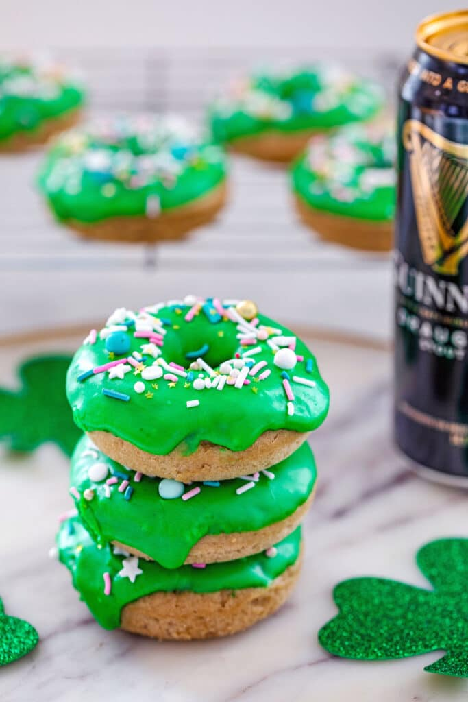 Stack of four Guinness doughnuts with baking rack with more doughnuts in the background, a tall can of Guinness beer and glitter shamrocks on marble surface