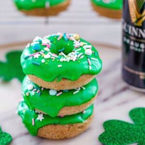 Stack of 3 Guinness doughnuts with bright green Irish whiskey frosting on a platter with Shamrock's and a can of Guinness with more donuts in the background