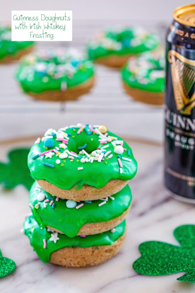 Stack of four Guinness doughnuts with baking rack with more doughnuts in the background, a tall can of Guinness beer, glitter shamrocks, and the recipe title at the top of the image