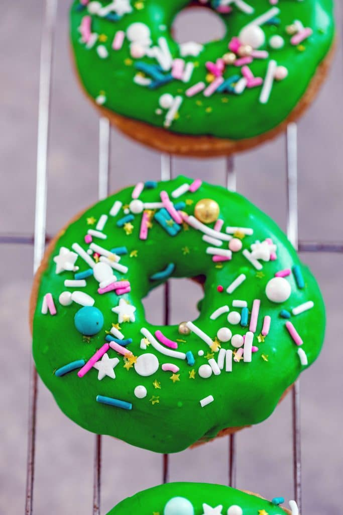 Overhead view of bright green Guinness doughnuts with colorful sprinkles on a baking rack