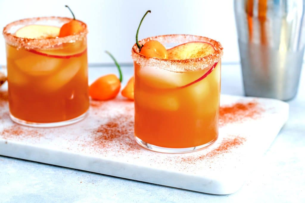 Landscape view of two habanero ginger apple cider cocktails on a marble surface sprinkled with cinnamon with habanero peppers and cocktail shaker in the background