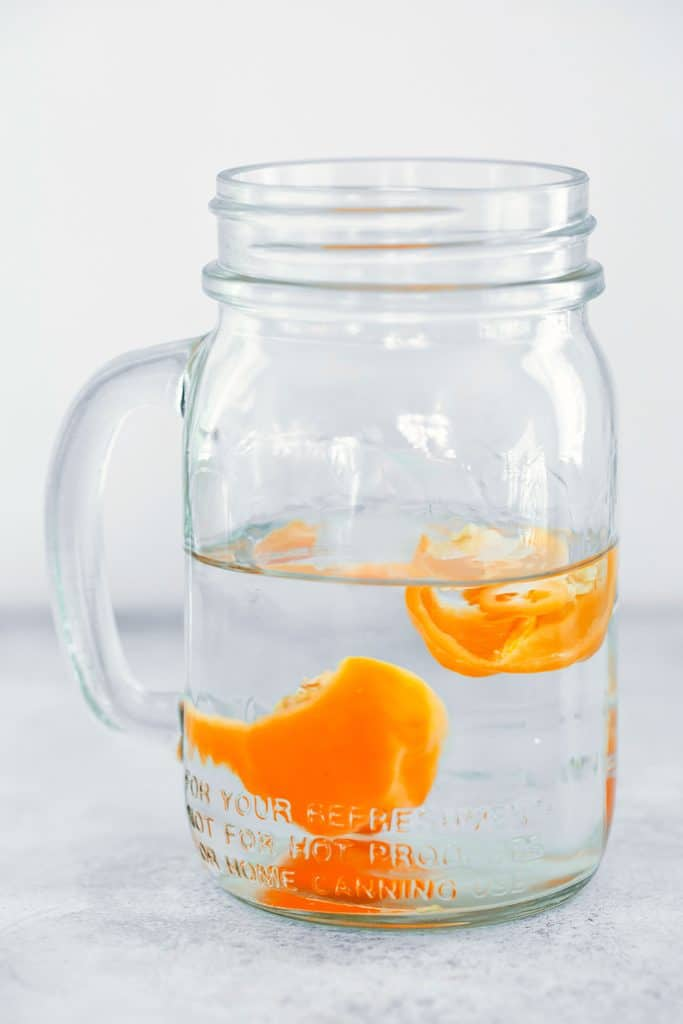 Head-on view of mason jar filled with tequila and habanero pepper halves