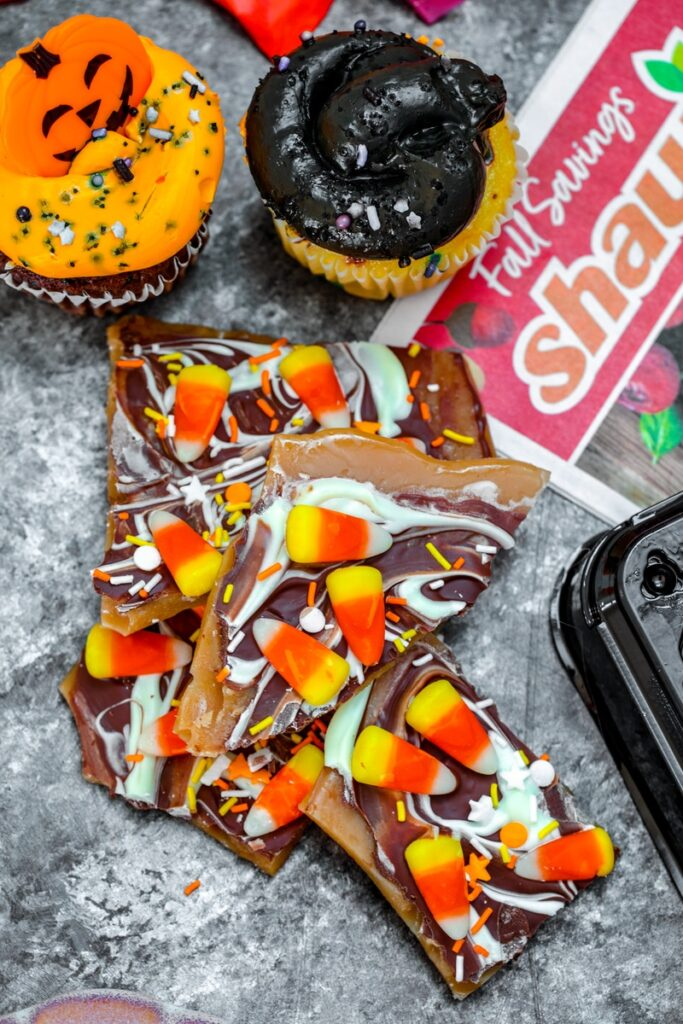 overhead view of candy corn toffee with cupcakes and Shaw's flyer in background