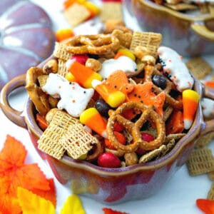 Overhead closeup view of a pumpkin bowl of Halloween trail mix with candy corn, pretzels, animal crackers, peanuts, and M&Ms