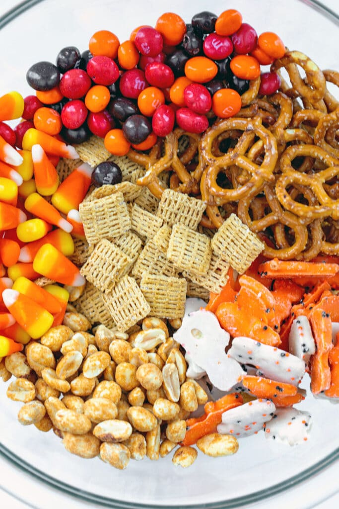 Overhead view of all Halloween trail mix ingredients in a big bowl, including cereal, peanuts, candy corn, M&Ms, pretzels, animal crackers