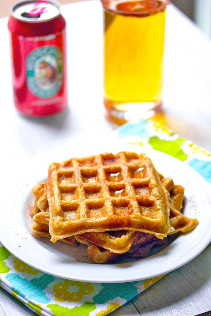 Head-on view of three hard cider waffles stacked on a plate with can of hard cider and glass of cider in the background