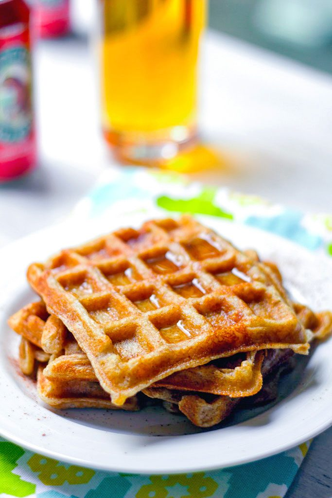 Close-up head-on view of a stack of three hard cider waffles on a plate with glass of hard cider in the background