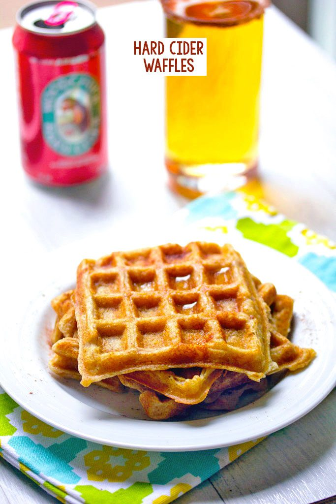 Head-on view of three hard cider waffles stacked on a plate with can of hard cider and glass of cider in the background and recipe title at top