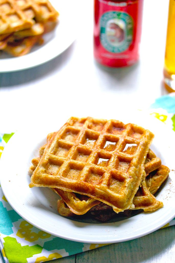 Overhead view of stack of three hard cider waffles stacked on a plate with second plate and can of hard cider in the background