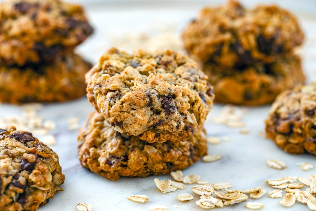 Landscape head-on view of multiple stacks of healthy chocolate chip oatmeal cookies on a marble surface with oats scattered around
