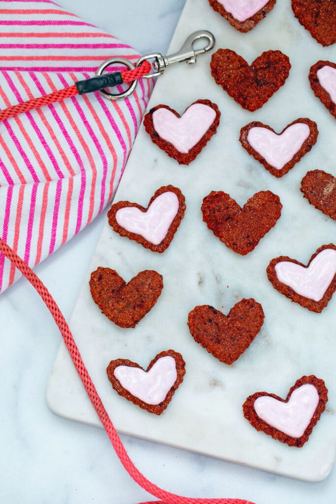 Lots of heart-shaped beet cookies for dogs, some frosted and some not, on marble platter with dog leash in background