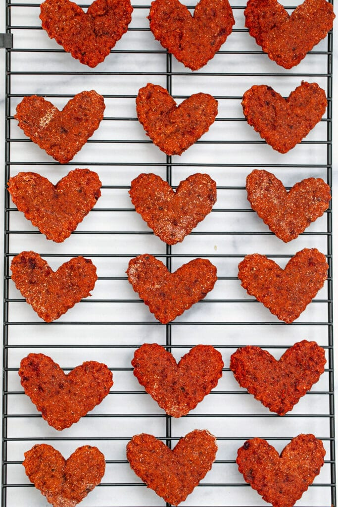 Heart-shaped beet cookies for dogs just out of the oven on baking rack