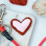 Close-up of heart-shaped beet cookie with sour cream icing and dog paw and leash in background