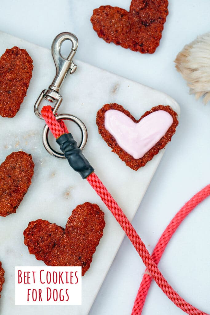 Heart-shaped beet cookies for dogs on marble tray with leash and dog paw in background and recipe title at bottom of image