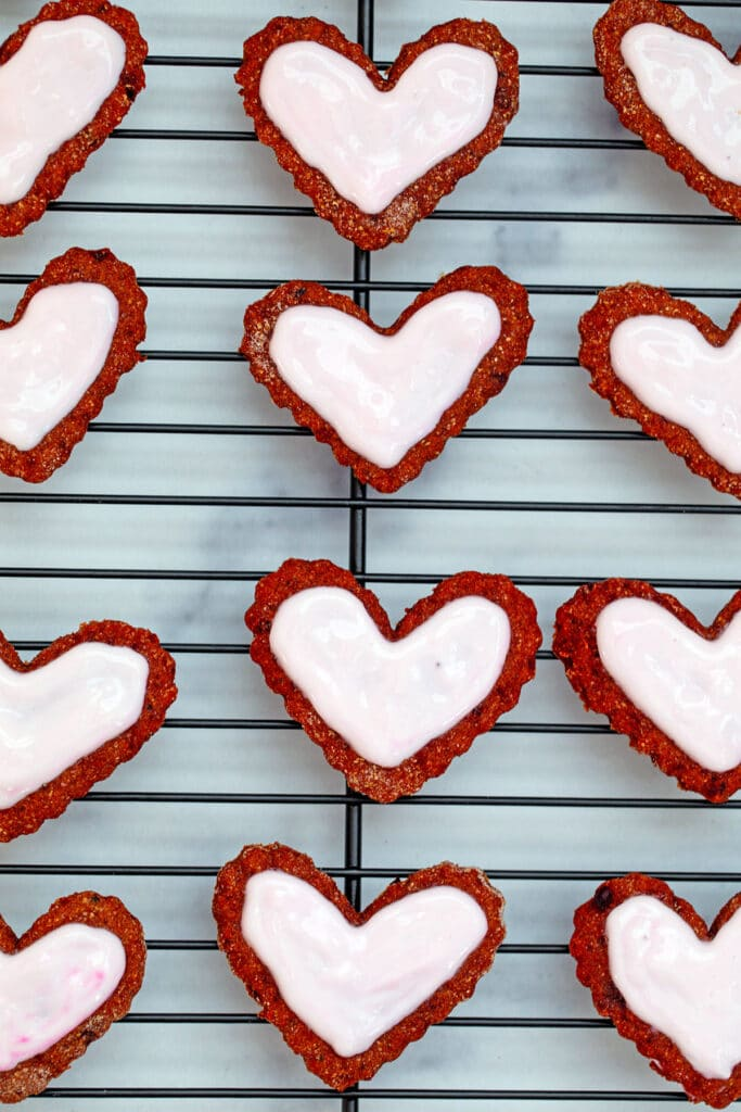 Heart-shaped beet cookies for dogs on baking rack topped with pink sour cream icing