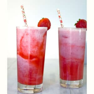 Head-on view of two homemade Starbucks Pink Drinks in tall glasses with straws and strawberry garnish