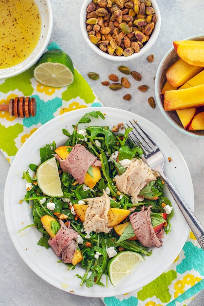 Overhead view of peach salad with roast beef turkey, and honey lime dressing on brightly colored towel with peach slices, lime, honey stick, bowl of dressing, and bowl of pistachios in the background