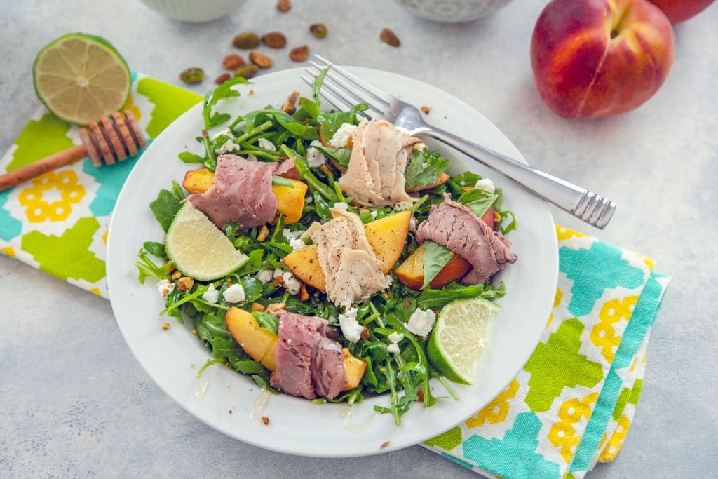 Landscape view of peach salad with roast beef and turkey in a white bowl on a brightly colored towel with honey stick, lime half, pistachios, and peach in the background
