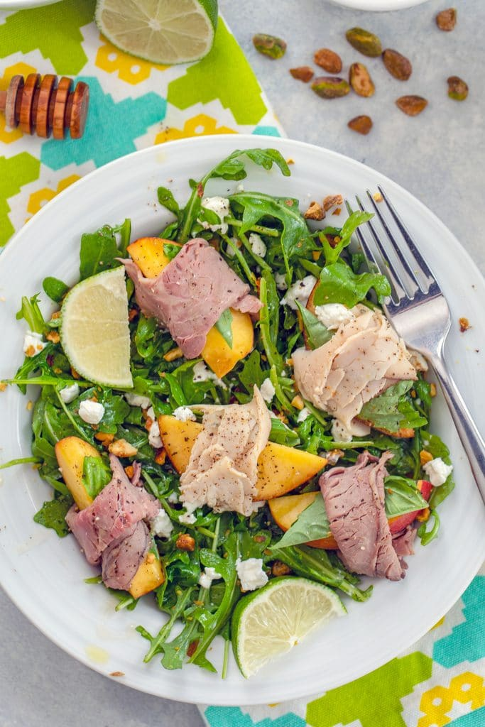 Close-up of peach salad with roast beef and turkey in a white bowl on a brightly colored towel with lime, honey stick, and pistachios in the background