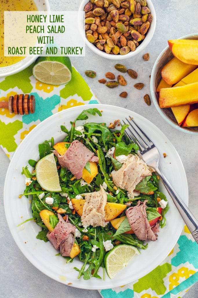 "Overhead view of peach salad with roast beef turkey, and honey lime dressing on brightly colored towel with peach slices, lime, honey stick, bowl of dressing, and bowl of pistachios in the background and ""Honey Lime Peach Salad with Roast Beef and Turkey"" text on top"