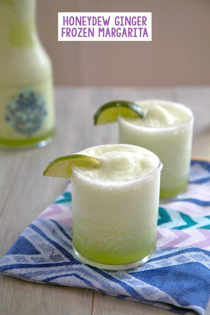 Head-on view of two bright green honeydew margaritas with lime wedge garnish on a colorful napkin with pitcher of margaritas in the background and recipe title at top