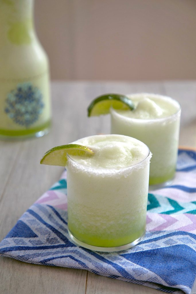 Head-on view of two bright green honeydew margaritas with lime wedge garnish on a colorful napkin with pitcher of margaritas in the background