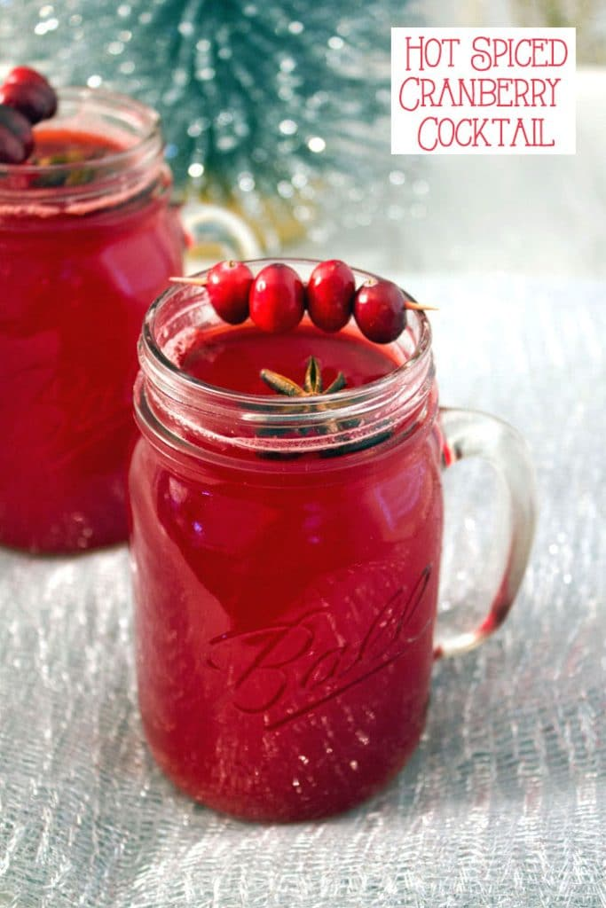 A mason jar filled with hot spiced cranberry cocktail with star anise and cranberry garnish with a second cocktail and tinsel in the background with recipe title at the top of the image
