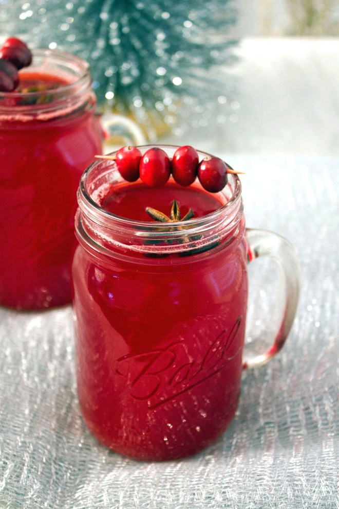 A mason jar filled with hot spiced cranberry cocktail with star anise and cranberry garnish with a second cocktail and tinsel in the background